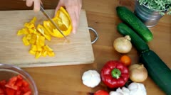 Stock Video Footage of Female hands slicing yellow pepper, top view HD