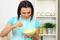 Young happy woman preparing and tasting food in the kitchen NTSC Stock Footage