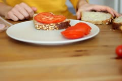 Female hands preparing sandwich with ham and tomatoes, steadicam shot NTSC Stock Footage