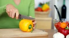 Stock Video Footage of Female hands slicing yellow pepper in half HD