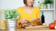 Young woman spreading butter on loaf of bread, steadicam shot HD Stock Footage