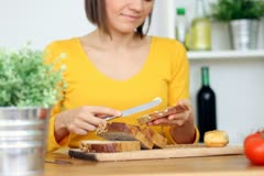 Young woman spreading butter on loaf of bread, steadicam shot NTSC Stock Footage