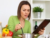 Stock Video Footage of Woman cooking, tasting and looking at recipe on digital tablet NTSC