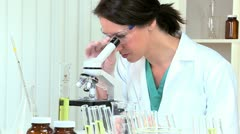 Medical Researcher Studying Specimens with Microscope - stock footage