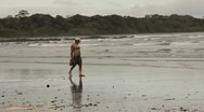 Man carrying shoes walking along the beach Stock Footage