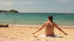 Woman sitting on the beach taking her hair out of  pony tail Stock Footage