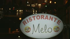 Rack focus Italian restaurant sign to traffic Stock Footage