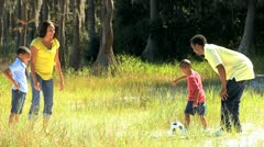 Young Family Kicking a Ball in the Park - stock footage