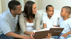 Young Ethnic Family Looking at Photograph Album Stock Footage