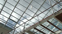 Clouds time lapse view seen through glass roof of modern building Stock Footage