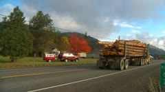 Log truck pass on narow rural highway Stock Footage