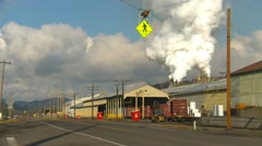 Steam rising lumber mill with tractor and railcars Stock Footage