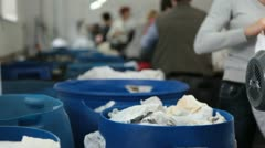 Workers drop rags into plactic boxes in recycling factory. Stock Footage