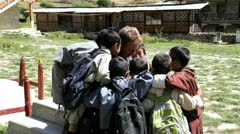 Photographer talking to young children in a group, Bhutan, Asia Stock Footage