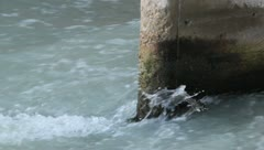 Water flowing past a pillar on a bridge Stock Footage