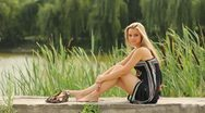 The beautiful girl sitting near the river Stock Footage
