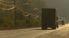 late afternoon transport trucks on narrow highway backlit - stock footage