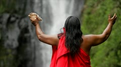 Stock Video Footage of A Hawaii native holds out his hands to bless a waterfall.