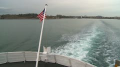 Ferry, stern aft wake and US flag Stock Footage