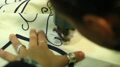 Expert seamstress weaves a written Stock Footage