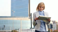 Young pretty businesswoman reading the newspaper in the city HD Stock Footage