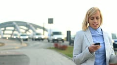 Happy businesswoman sending sms, texting by the city street HD Stock Footage