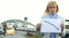 Attractive businesswoman holding downward graph by the street HD - stock footage