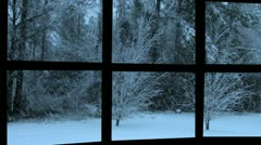 Snowing at dusk seen through a black metal window Stock Footage