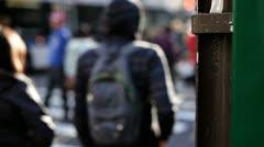Pedestrians crossing street focus on post Stock Footage