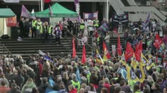 Striking workers listen to speeches at a rally Stock Footage