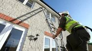 Construction. Workman climbing ladder on new build house. Stock Footage