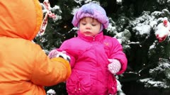 Little girl came and gives snow to another kid in pink down-padded coat Stock Footage