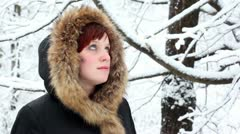 Girl in fur hood looks at falling snow Stock Footage