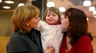 Stock Video Footage of Grandmother and mother kiss little girl inside cafeteria