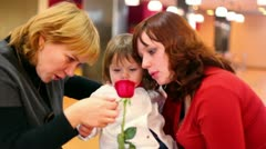 Two females and little girl look on rose Stock Footage
