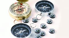 Nine small black plastic compasses, two big and one vintage golden Stock Footage