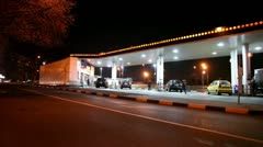 Several cars fill fuel at gas station in city at night Stock Footage
