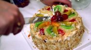 Stock Video Footage of Hands severs sweet fruit cake by knife