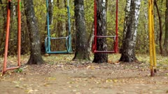 Pair of empty metallic swing sway on grove Stock Footage