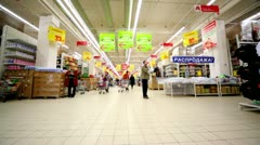 People walk at hypermarket Auchan in trade center Troika Stock Footage