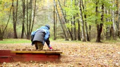 Boy plays sand on playground in park Stock Footage