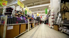 Few people walk among shelves with goods in hypermarket Auchan Stock Footage