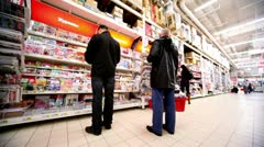 Several people choose magazines on showcase in hypermarket Auchan Stock Footage