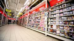Showcase with dvd discs with varius films in hypermarket Auchan Stock Footage