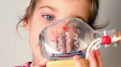 Girl hold and looks at model of tallship in glass bottle Stock Footage