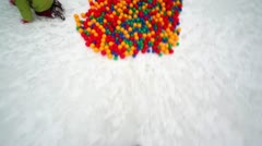 Legs runs into pile of colored balls Stock Footage