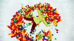 Little girl lying in pile of colored balls in snow hollow Stock Footage