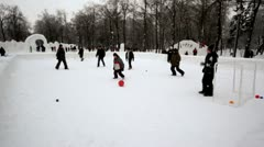 Kids play football in park at winter day, people walk around, corner view Stock Footage