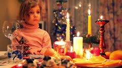 Girl sits at decorated christmas dining table with fruit, candy, candles Stock Footage