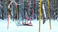 Two empty metallic swing sway in park Stock Footage